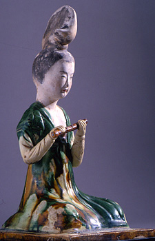 Figure of a kneeling female musician with a distinctive high chignon hairstyle, holding a flute. This would have been one of a group of musicians representing a courtly ensemble that would have been placed in the tomb of a deceased member of the imperial family. Country of Origin: China. Date/Period: Tang dynasty, AD 618-906. Material Size: glazed pottery. Credit Line: Werner Forman Archive/ Idemitsu Museum of Arts, Tokyo . Location: 05.