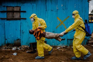 MONROVIA, LIBERIA - SEPTEMBER 05, 2014: James Dorbor, 8, suspected to have Ebola, is rushed in by medical staff wearing protective clothing into the JFK Ebola treatment centre on September 05, 2014 in Monrovia, Liberia. James Dorbor, 8, had been sick and showing symptoms of Ebola for previous 3-4 days - extreme weakness, loss of appetite, toileting and vomiting.. Edward, James father first took the boy to the S.O.S clinic, nearby for treatment, but being an ordinary hospital medical staff were too afraid to treat the boy. Edward then walked James to the JFK Ebola treatment facility nearby. That day the scene outside of the JFK was chaotic. One boy lay dead in the back of an ambulance, as three of his family members sat inside with the body. Two family members lay in the back of a taxi unable to move. Others lay strewn on the dirt, underneath a shelter, too weak to stand, some laying on benches. James lay on the dirt outside of the JFK centre for hours waiting to be admitted. Edward fought hard to get his son to drink fluids but to no avail. At one point James convulsed for a few minutes and then lay motionless. Onlookers gasped and Edward reacted believing that his son had passed, but the boy still hung on for a few more hours. Late in the afternoon, the gates opened and the waiting people rushed in to the clinic leaving James on the ground as he was unable to move on his own. His father was too afraid to carry him as he only had a pair of gloves on and onlookers were already worried that he had had too much contact with his son. Edward ran to he heavy gate and beat on the door to get attention and informed them frantically of James condition. It took health workers some time to dress themselves in protective clothing and then rushed the boy inside once the area had been sprayed with chlorine surrounding the boy. According to health officials, James passed away shortly after being admitted.