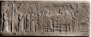 Stone relief from the palace of Ashurbanipal. Ashurbanipal and his queen feasting in a garden following the defeat and death of the Elamite king Teumman at the battle of Til-Tuba in 653. Teumman's head is hanging in the tree on the left. Culture: Assyrian. Date/Period: Late Assyrian, c.645 BC. Place of Origin: Nineveh, Assyria, Ancient Iraq. Material Size: Stone. Credit Line: Werner Forman Archive/ British Museum, London . Location: 15.
