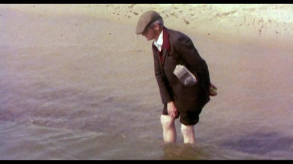 Man in a flat cap wading in the sea