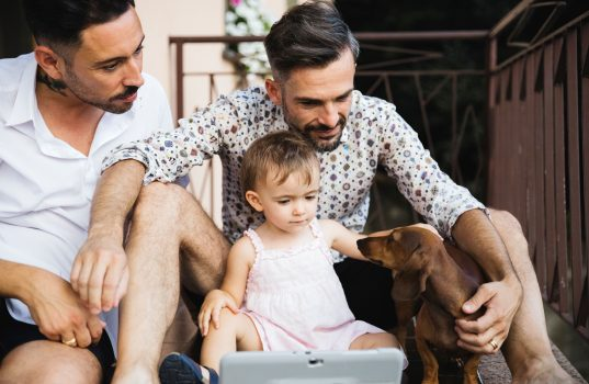 Male gay couple with young child and dog