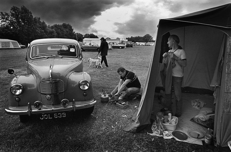 Two men campers prepare breakfast at the Sandy Balls campsite beside their vintage Austin A40 Devon car. A dog walker and storm clouds in the background. First published in The Sunday Times Date: 1989