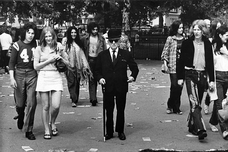 A cool City gent in smart suit, bowler hat and dark sunglasses stands at the centre of a group of young hippies with their long hair, jeans, teeshirts, ponchos and mini skirts. Date: early 1970s