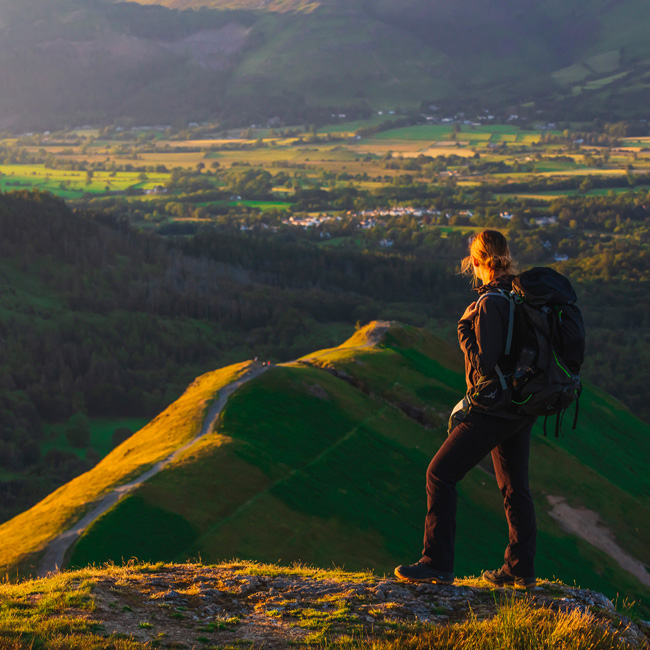 United Kingdom, England, Cumbria, Keswick, Great Britain, Lake District, British Isles, A woman hiking the hills of Derwent Water to the Cat Bells elevated viewpoint at sunset and enjoying the view of the Lake District