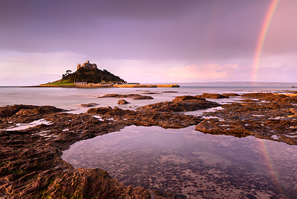 St Michael's Mount at sunrise with a rainbow over Penzance, Viewed from Marazion, West Cornwall, UK. February 2019.