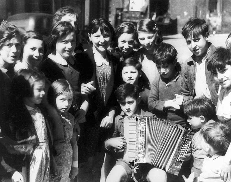 Italian immigrant children  playing with a concertina in  the Saffron Hill area, near  Farringdon, London EC1.       Date: 1930s