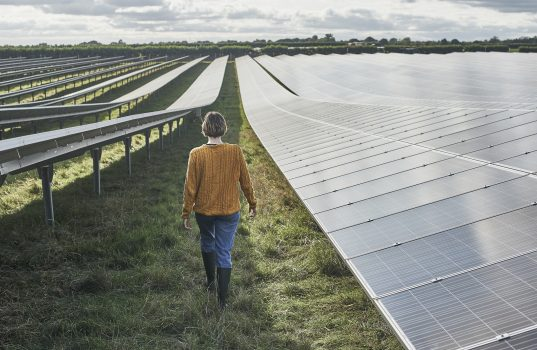 Young female farmer walking through solar farm ©Mike Harrington / Getty Images