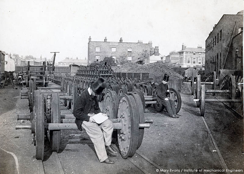 A view along the north side of the Great Eastern Railway?s Locomotive works at Stratford (East London) May 1864 with William Henry Maw, then Head of the Drawing office, seated on the axle of a carriage or wagon wheel set, with his colleague James Kitson further back. In the background is The Railway Tavern public house (which is still extant) and dwellings in the Angel Place area.     Date: 1864