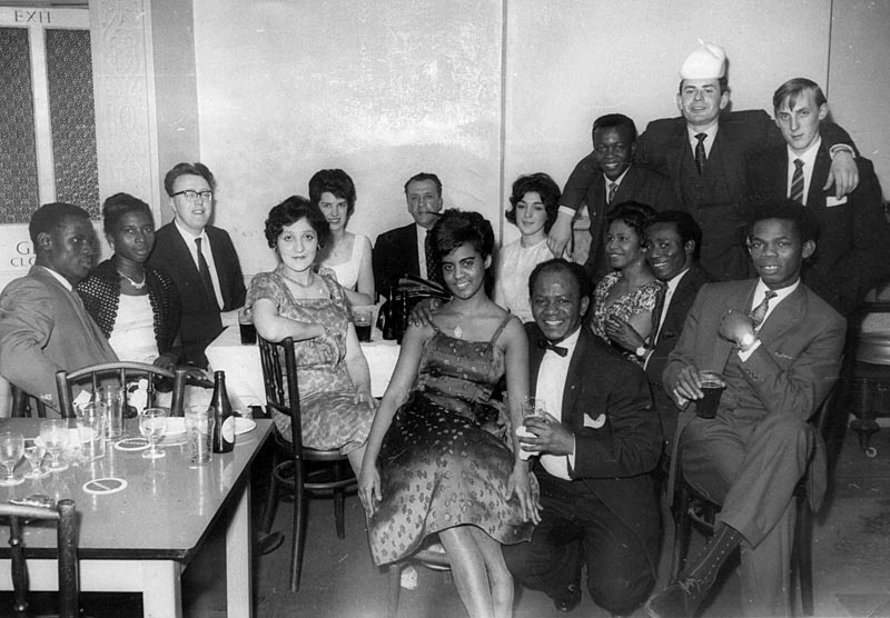 The gathering of 15 men and women from Nottingham's diverse communities at the British Consulate in Nottingham. Table left of picture with glasses and drinks. Date: 1960s