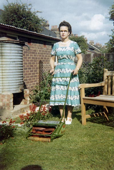 Smartly-dressed middle aged woman standing proudly (if slightly stifly) in a suburban garden with her lawnmower.