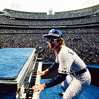 English singer songwriter Elton John performing at Dodger Stadium in Los Angeles, October 1975. He is wearing a sequinned baseball outfit.