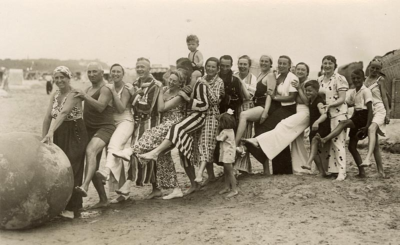 A wonderful photograph of a very jolly group (possibly one large extended family) playing with a huge ball on the beach - note the variety of magnificent beachwear on show!! Encapsulating the joy of the British seaside holiday in one image... circa 1930