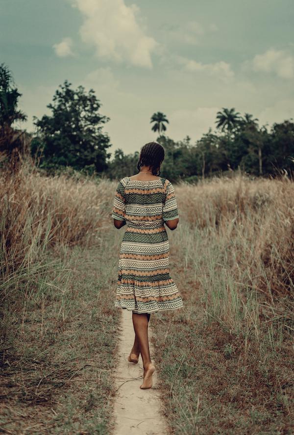 Nigeria, Delta state, Rear view of woman in patterned dress walking in field