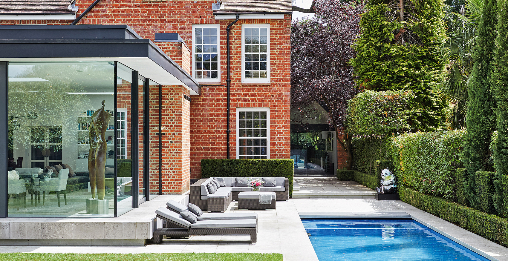 Exterior of house with dining room extension with glass wall, bespoke lap pool, a lawn and sun loungers