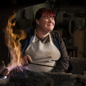 A female steel worker sat by a forge
