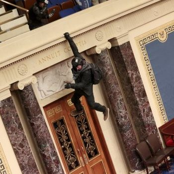 A protester is seen hanging from the balcony in the Senate Chamber on January 06, 2021 in Washington, DC.