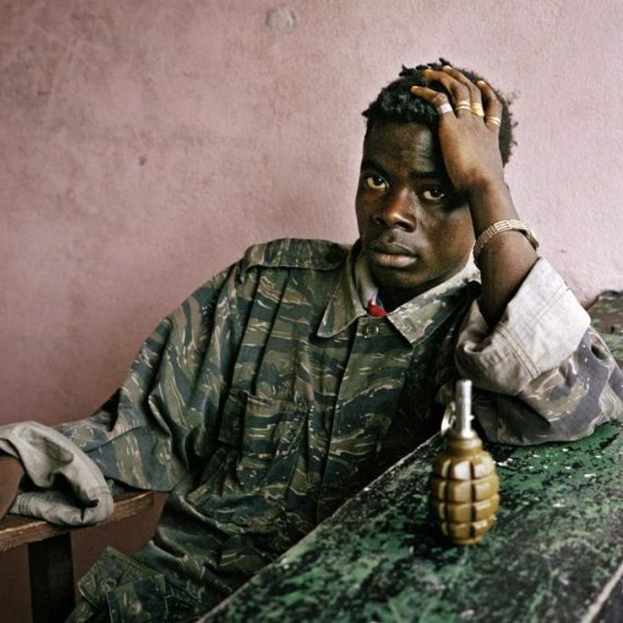 Young rebel fighter and hand grenade, Tubmanberg, Liberia. June 2003. Photograph by Tim Hetherington